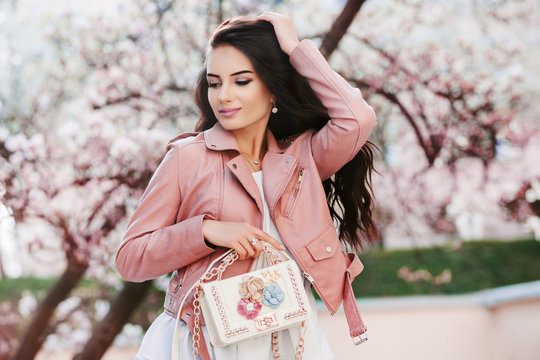 Outdoor portrait of yong beautiful fashionable girl holding white bag, wearing pink leather jacket. Blooming tree on background. Spring fashion concept. Copy, empty space for text