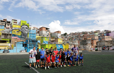 An amateur soccer team pose for a photograph with the image of Brazil' soccer player Gabriel Jesus painted on the walls of houses in the neighbourhood he lived in during his childhood in Sao Paulo