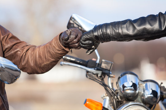 Close up of bikers hands in leather gloves with repay salutation