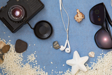 Camera and sunglasses on the sand. Summer vacation concept