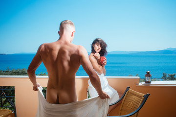Couple in love drinking coffee on balcony, nature and sea on background. Man and lady in bathrobe hold cup and drink. Vacation and relax concept. Couple enjoy view on sea and skyline on sunny day