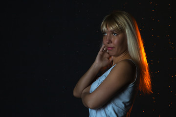 Girl in the white shirt and water drops behind and arround her illuminated by light during a photoshoot with water