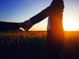in love The guy and the girl run around the field at sunset. Silhouettes of a loving couple. Lovers holding hands