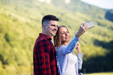 Cute young couple taking selfie outdoor