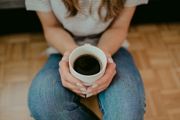 Young attractive girl holding white coffee mug in her hands while sitting on cozy bedroom wooden floor.