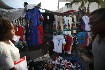 People walk past football jerseys hanging on display for sale at a street stand in Port-au-Prince