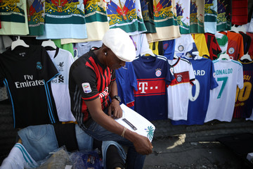 A vendor folds a t-shirt next to football jerseys on display for sale at a street stand in Port-au-Prince