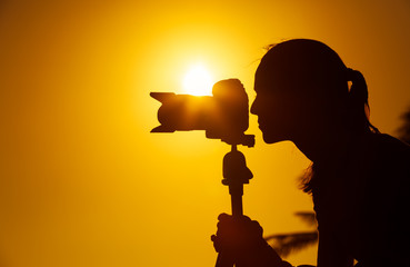 Female photographer taking pictures at sunset. Photography and the arts concept.