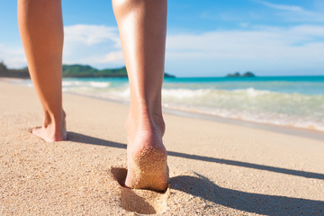Feet walking on a beautiful white sand beach. Holiday, and exotic vacation concept. Location Hawaii.