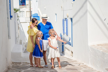 Parents and kids taking selfie photo background Mykonos town in Greece