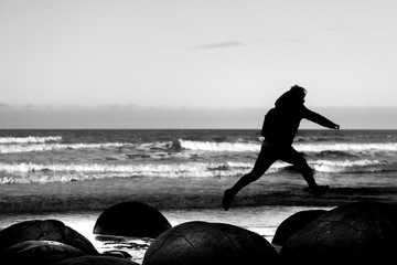 Jumping on Dunedin Boulders  with Black and White tone