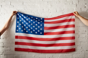 cropped image of man and woman holding american flag against brick wall