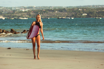 beautiful female surfer in bikini with surfboard walking on beach