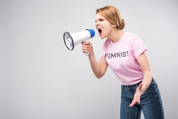 woman in pink feminist t-shirt yelling at megaphone, isolated on grey