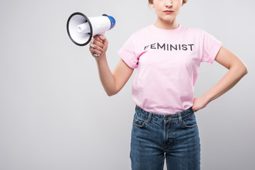 cropped view of woman in pink feminist t-shirt holding megaphone, isolated on grey