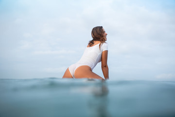 attractive young woman in wet white swimsuit sitting on surfboard in ocean