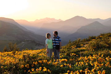Happy friends surrounded by blooms. Smiling man and woman looking at each other on arnica meadow in bloom. Travel Pacific Northwest. Washington State. United States of America