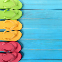 Side border row of flip-flops on blue background wood beach decking