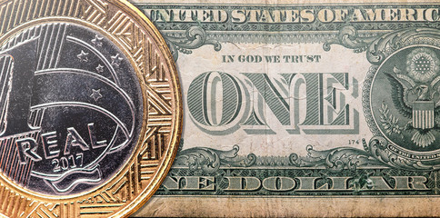 One Brazilian Real coin overlaped on a one US American Dollar bill, exchange rate and economy concept idea