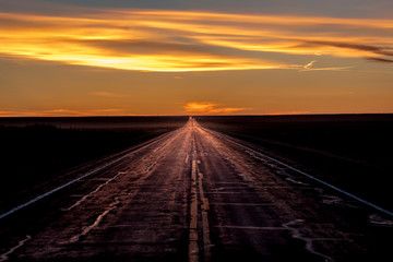 MARCH 8, 2017, NEBRASKA - Sunset over Rural Farm Country Road with pickup truck driving by row of powerlines