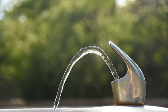 Outdoor Water Fountain with Flowing Water against Blurred Outdoors Background
