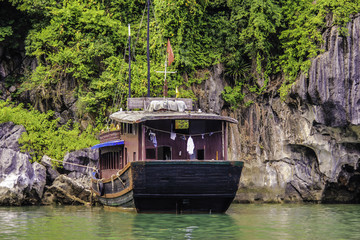Traditional House Boat with a Clothesline on the back Parked in front of One of Limestone Mountains in Halong Bay, Vietnam