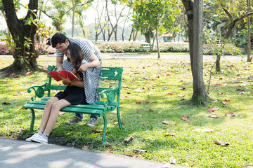 Couple in park sitting on a bench. Talking to each other in romantic and intimate mood. Chinese people.