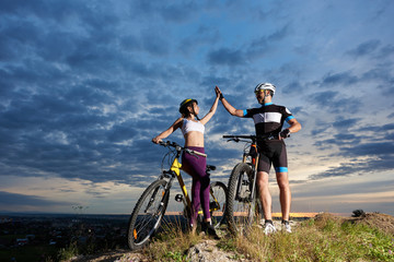 Pair of cyclists on top of a mountain give each other a high five against a cloudy sky at sunset and a town in the valley. Guys with bicycles, dressed in sports clothes and helmets