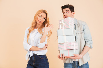 Portrait of caucasian woman expressing outrage and rejection while handsome man giving her lots of present boxes, isolated over beige background