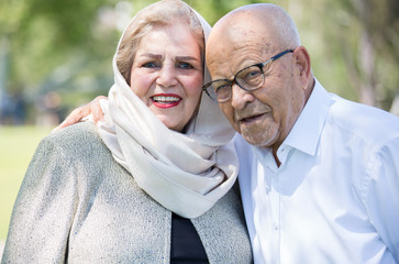 Closeup portrait, retired couple in white shirt and dress holding each other smiling,enjoying life together, isolated outside green trees background.