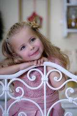 cute little blonde girl in pink dress with beautiful haircut