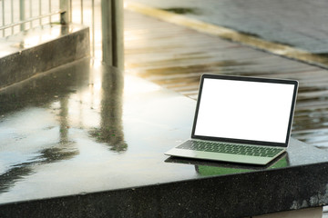 The laptop located behind the rain. The sun is bright. Copy space.
