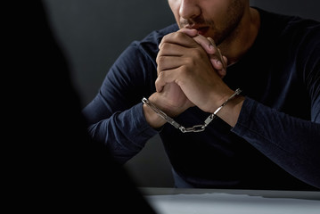 Criminal man with handcuffs in interrogation room