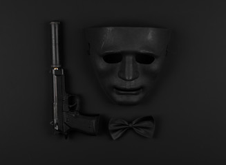 pistol with a silencer and a black mask on a black isolated background
