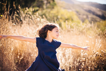 Girl dancing in the sun with outstretched hands