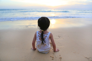 Rear view of asian girl sitting on the beach at the sunset.