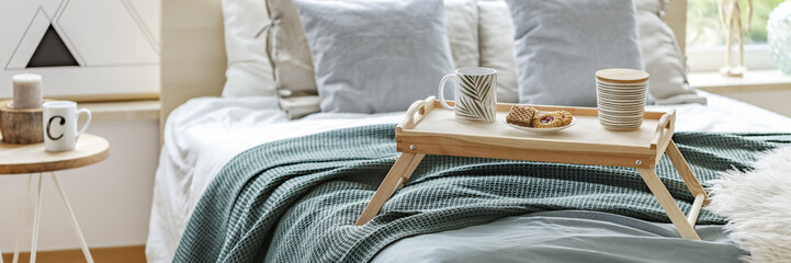 Wooden breakfast tray on bed