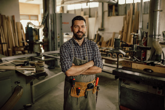 Portrait of a smiling young woodworker standing with his arms crossed by a bench saw in his workshop full of carpentry equipment