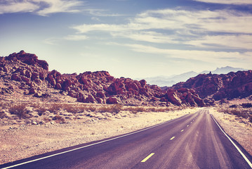 Retro toned desert road, travel concept, Valley of Fire; Nevada, USA.