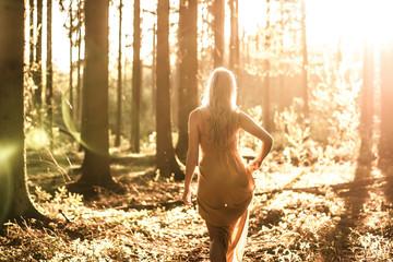 Frau im Wald spaziert dem Sonnenuntergang entgegen