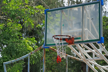 Basketball hoop on clear acrylic. Outdoors in parks, community green trees around the field. For people in the community to play a sport is free. To promote good health