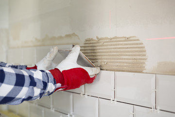 Process of tiling the tiles in the kitchen. Home improvement, renovation concept