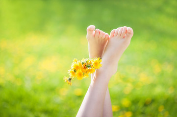 Children's legs hold a bouquet of dandelions on the background of dandelion fields in the light of the sunset sun