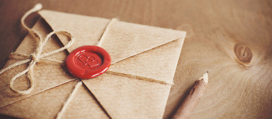 love letter in a craft envelope with a sealing wax seal in the form of a heart on a wooden...
