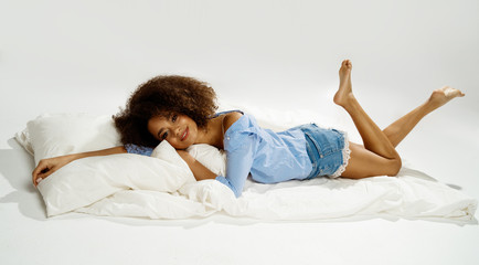 Beautiful african american girl with an afro hairstyle smiling and lying in bed
