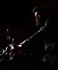 Hipster, brutal biker in leather jacket riding motorcycle at night time, copy space. Man with beard, biker in leather jacket sitting on motor bike in darkness, black background. Night rider concept.