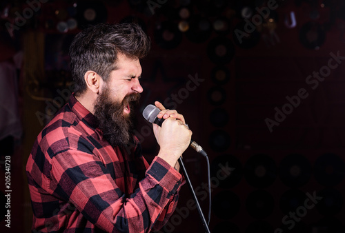 Man with tense face holds microphone, singing song, black background