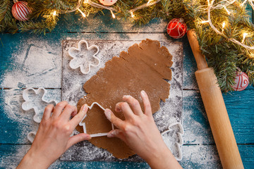 Photo of human hands, rolling pin, dough, spruce branches, garlands, biscuit molds