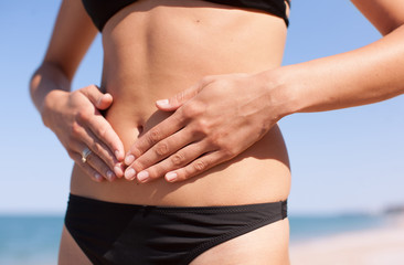 Girl in bikini posing with her fingers on her abdomen
