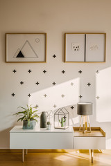 Framed posters on a white wall with plus sign pattern and a scandinavian sideboard in a bright, modern bedroom interior